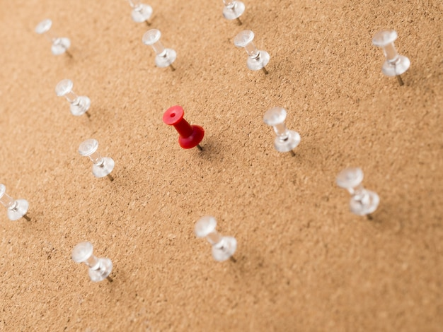 Low angle red pin surrounded by white pins on wooden board Free Photo