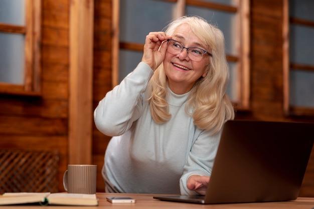 Low angle senior woman working on laptop Free Photo