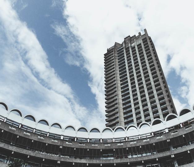 Inquadratura dal basso del barbican centre di londra con un cielo blu nuvoloso Foto Gratuite