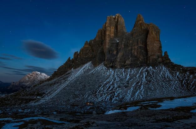 Colpo di angolo basso di una bella scogliera rocciosa coperta di neve sotto il cielo scuro Foto Gratuite