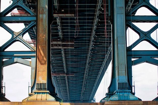 Colpo di angolo basso di un grande ponte di metallo blu in una giornata di sole Foto Gratuite
