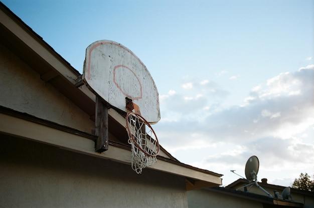 Inquadratura dal basso di un canestro da basket rotto sulla parte superiore di una casa Foto Gratuite