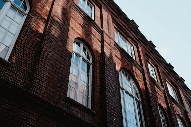Low angle shot of a brown concrete building with arch windows Free Photo
