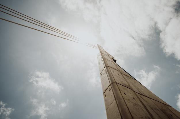 Inquadratura dal basso di una colonna di cemento con cavi contro un cielo nuvoloso luminoso Foto Gratuite