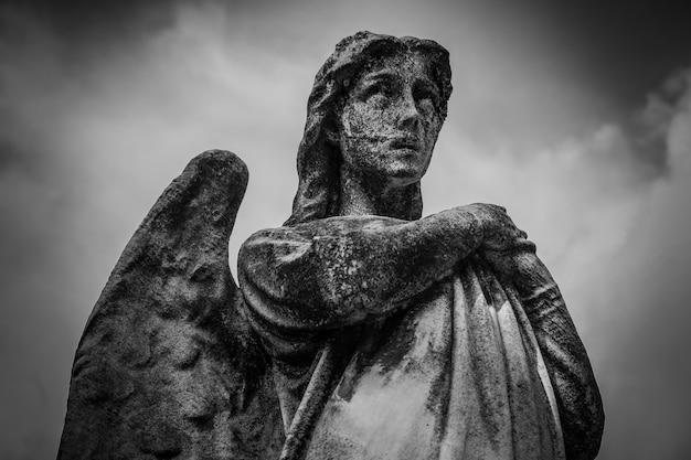Colpo di angolo basso di una statua femminile con le ali in bianco e nero Foto Gratuite