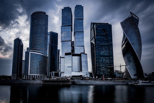 Low angle shot of grey skyscrapers in front of the river under the dark cloudy sky Free Photo
