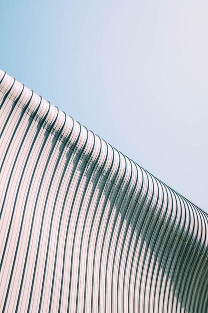 Colpo di angolo basso di un tetto di costruzione grigio e bianco con trame interessanti sotto il cielo blu Foto Gratuite
