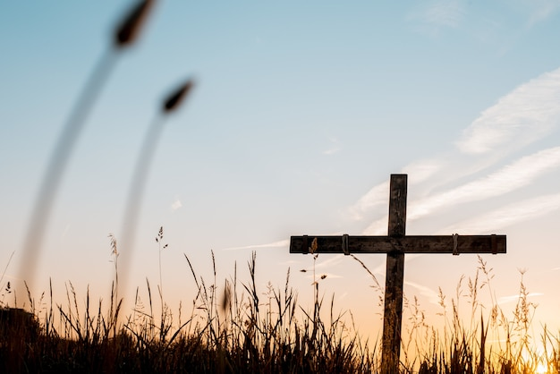 Low angle shot of a handmade wooden cross in a grassy field with a beautiful sky Free Photo