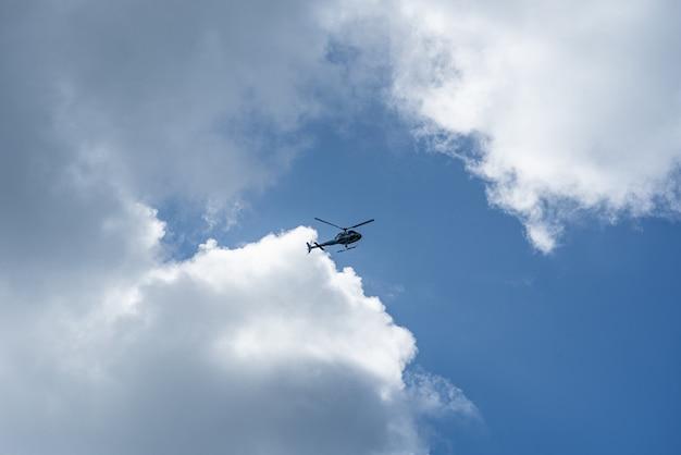 Inquadratura dal basso di un elicottero nel cielo nuvoloso Foto Gratuite