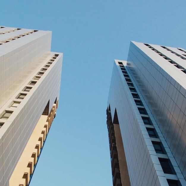 Inquadratura dal basso di grattacieli sotto un cielo blu chiaro Foto Gratuite