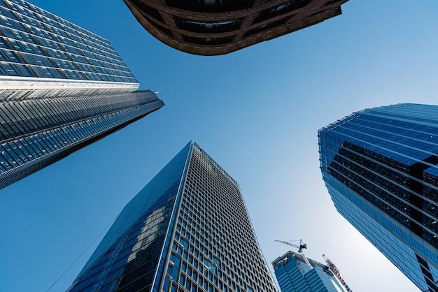 Inquadratura dal basso dei moderni edifici in vetro e grattacieli in una giornata limpida Foto Gratuite