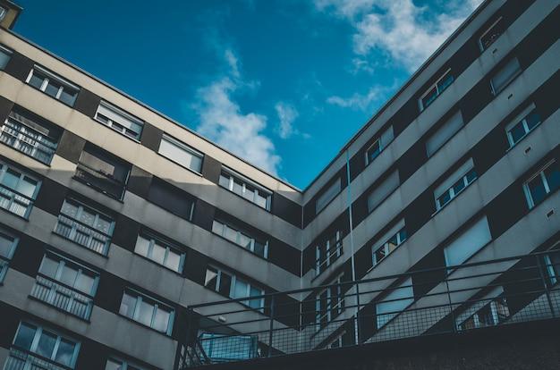 青い空の下で窓のある茶色と白の建物のローアングルショット 無料写真