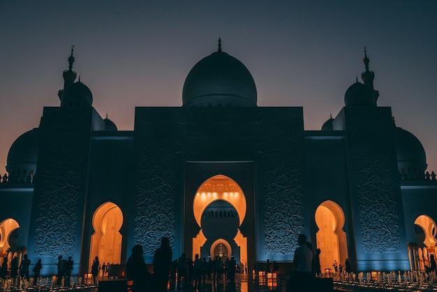 アブダビのグランドモスクのローアングルショット。建物の中に光るライトがあります。 無料写真