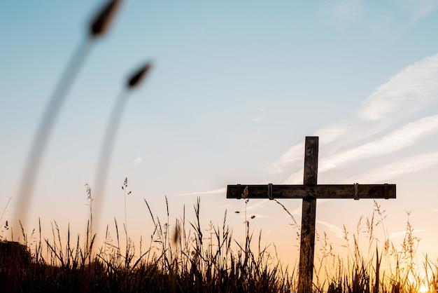 아름다운 하늘과 잔디 필드에서 수제 나무 십자가의 낮은 각도 샷 무료 사진