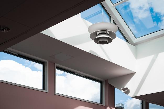 유리 천장이있는 건물 내부에 매달려있는 램프의 낮은 각도 샷 무료 사진