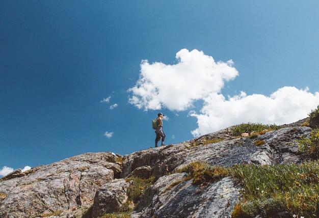 曇り空の下で山の端にバックパック立って男性のローアングルショット 無料写真