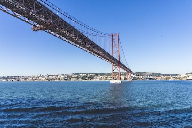 遠くに街のある水に架かるポンテ25デアブリル橋のローアングルショット 無料写真