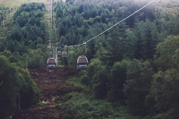 Низкий угол выстрела канатной дороги посреди зеленых горных пейзажей Бесплатные Фотографии