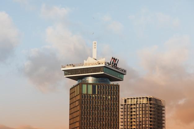 アムステルダムの曇り空の下にある背の高い歴史的建造物のローアングルショット 無料写真