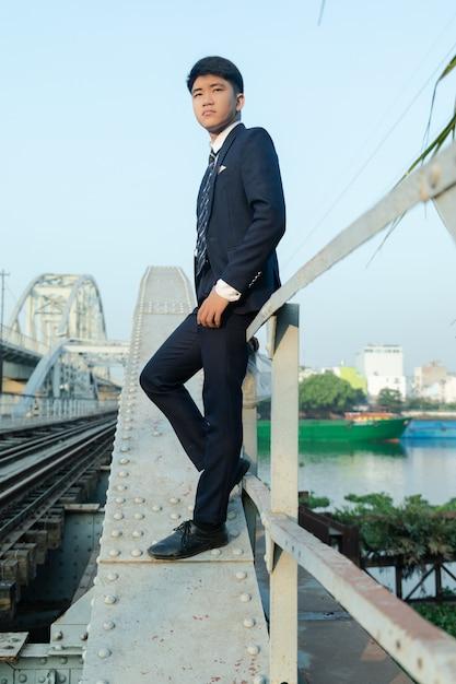 橋の手すりにもたれてスーツを着た若いアジア人のローアングルショット 無料写真