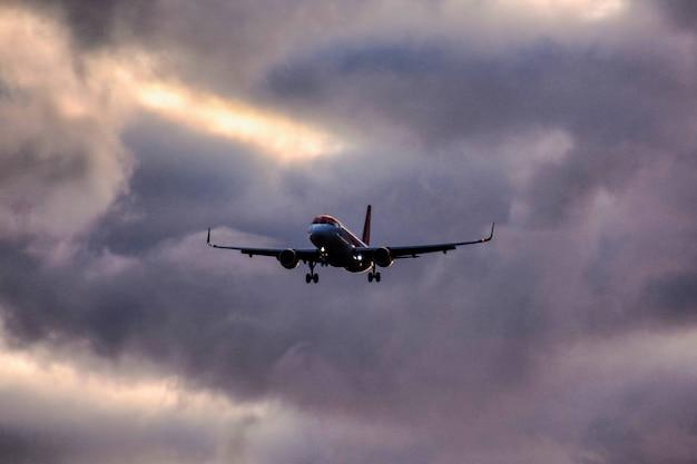 Снимок самолета, спускающегося с облачного неба под низким углом Бесплатные Фотографии