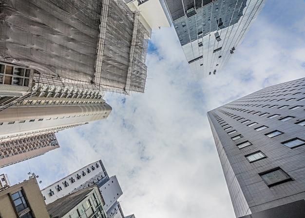 Низкий угол обзора высоких жилых домов под облачным небом Бесплатные Фотографии