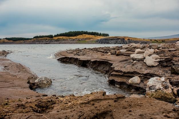 春の暗い雲と湖の岩の多い海岸のローアングルショット Premium写真