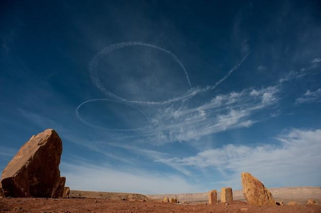 Снимок под низким углом спиральных белых следов в небе в пустыне Бесплатные Фотографии