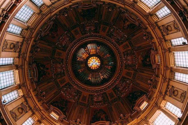 Низкий угол выстрела красивой живописи и окон на потолке в старом здании Бесплатные Фотографии