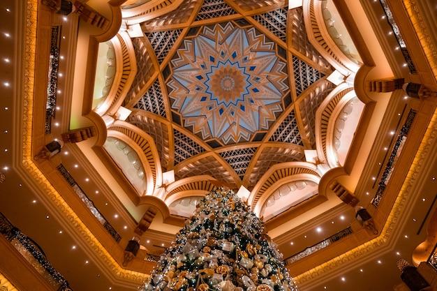 아랍 에미리트 아부 다비의 에미레이트 팰리스에서 크리스마스 트리의 낮은 각도 샷 무료 사진