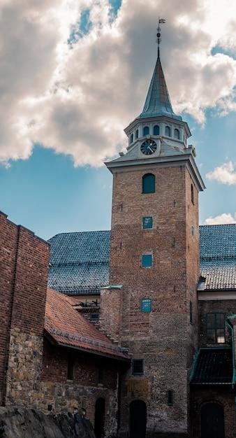 Низкий угол выстрела исторической крепости акерсхус под красивым облачным небом в осло, норвегия Бесплатные Фотографии