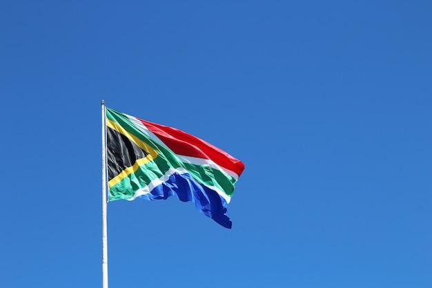 Снимок южноафриканского флага под низким углом на ветру под чистым голубым небом Бесплатные Фотографии
