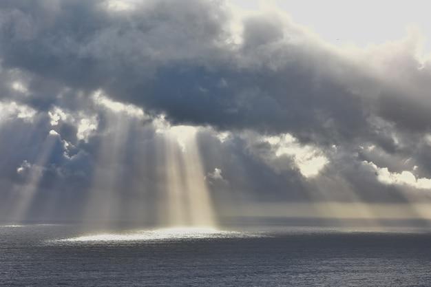 美しい海の上の雲を通して輝く太陽のローアングルショット 無料写真