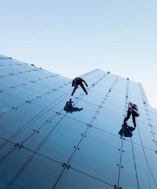 Снимок двух человек, спускающихся по спуску сбоку от высокого здания, под низким углом. Бесплатные Фотографии