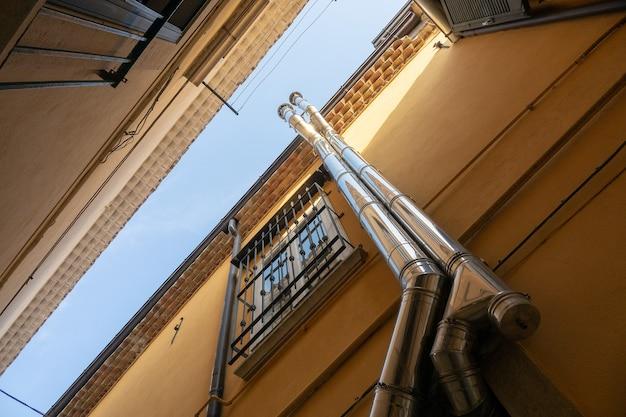 창문 옆에있는 건물 위로 올라가는 두 파이프의 낮은 각도 샷 무료 사진
