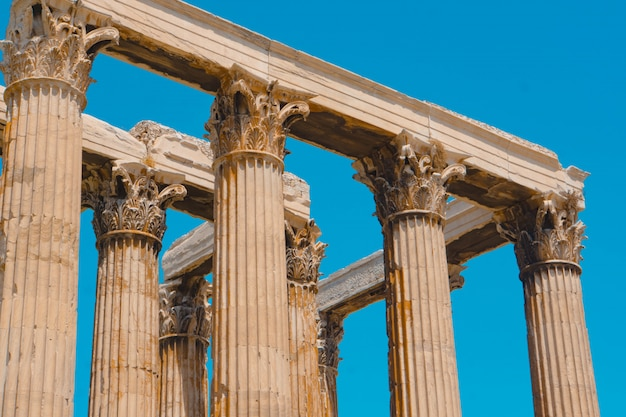 Low angle shot of old greek stone pillars with a clear blue sky Free Photo