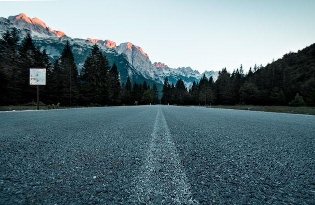 Low angle shot of road in forest with mountains in distance in valbona valley national park albania Free Photo