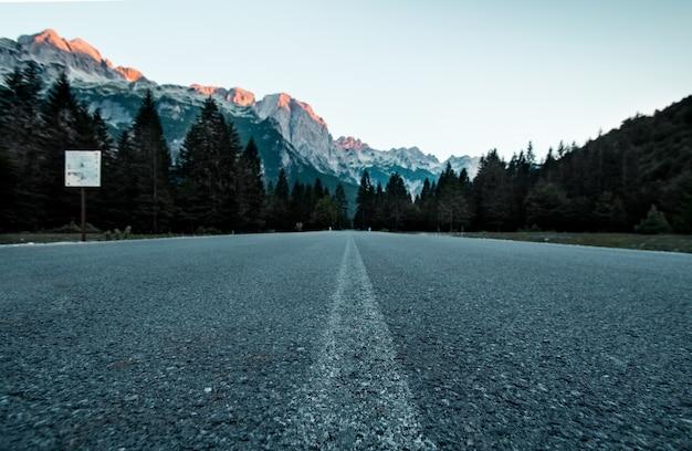 Inquadratura dal basso della strada nella foresta con le montagne in lontananza nel parco nazionale della valle di valbona in albania Foto Gratuite