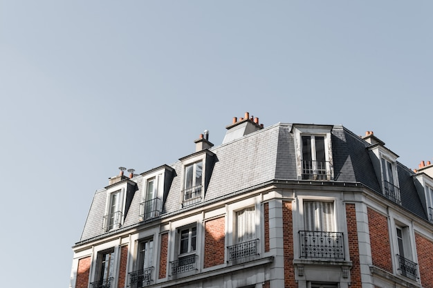 Low angle shot of the roof of a beautiful building with balconies in paris Free Photo
