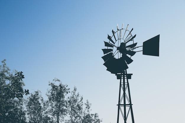 Inquadratura dal basso della silhouette di un mulino a vento sugli alberi Foto Gratuite