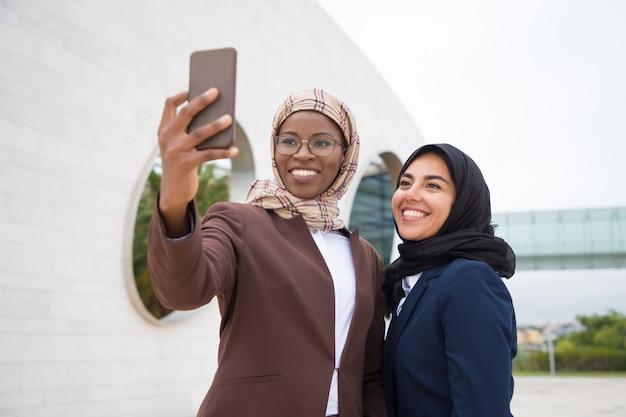 Low angle shot of smiling muslim businesswomen taking selfie Free Photo