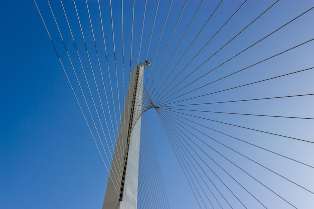 Low angle shot of steel cables with a clear blue sky Free Photo