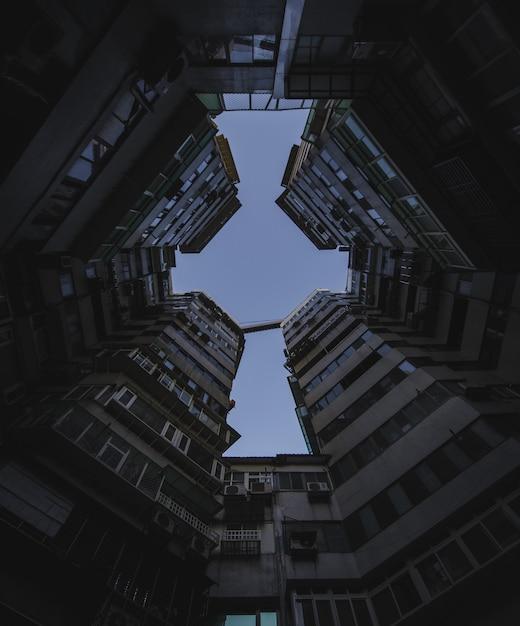 Colpo di angolo basso delle costruzioni di appartamento alte sotto il cielo scuro Foto Gratuite
