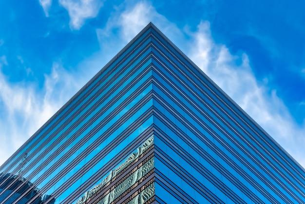 Inquadratura dal basso di un edificio in vetro alto sotto un cielo nuvoloso blu Foto Gratuite