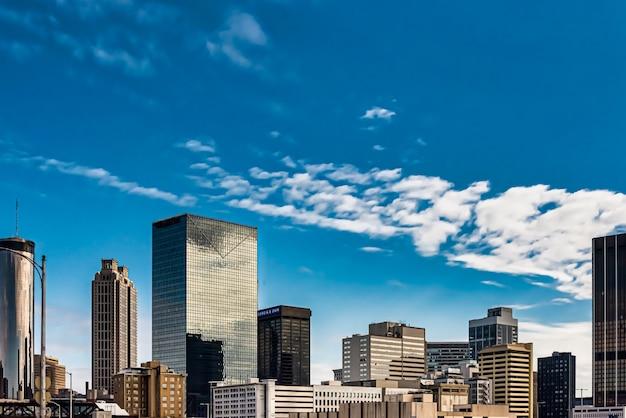 Colpo di angolo basso di edifici di vetro alti sotto un cielo nuvoloso blu Foto Gratuite