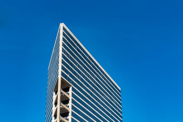 Inquadratura dal basso di edifici di vetro alti sotto un cielo blu nuvoloso Foto Gratuite
