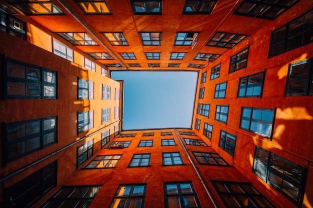 Inquadratura dal basso di un edificio arancione unico e alto che tocca il cielo Foto Gratuite