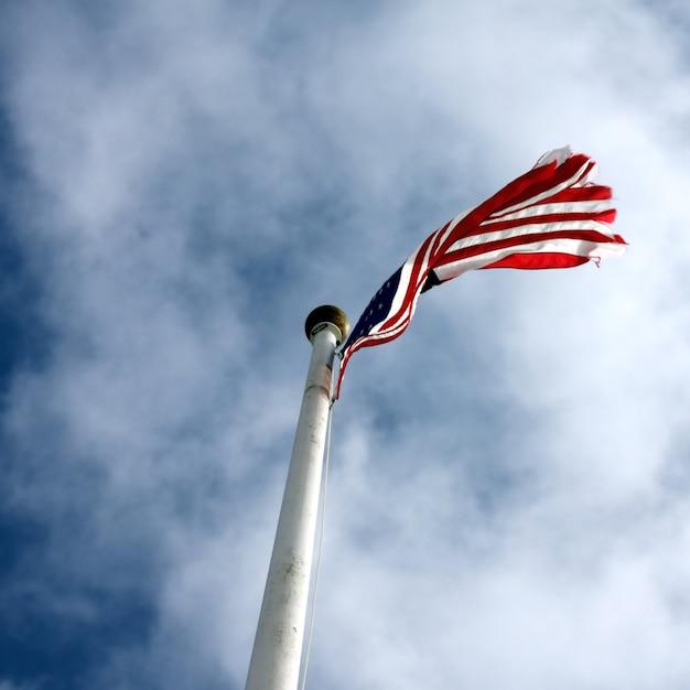 Inquadratura dal basso di una bandiera degli stati uniti con un cielo blu nuvoloso Foto Gratuite