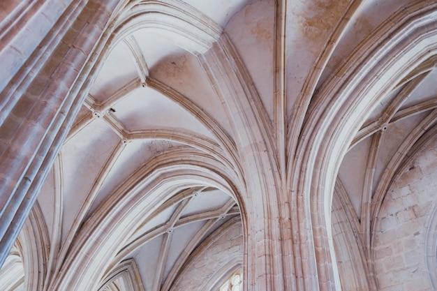 Colpo basso angolo delle colonne bianche e il soffitto di un vecchio edificio Foto Gratuite