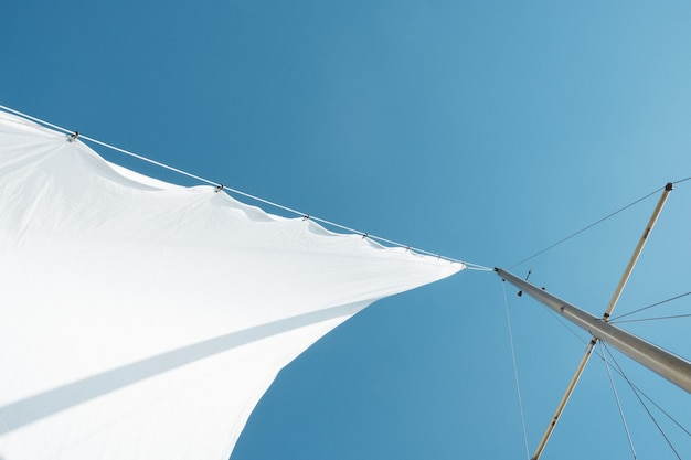 Low angle shot of a white sail on boat mast under clear sky during daytime Free Photo